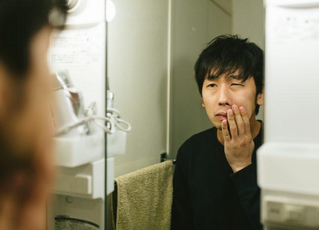 鏡の前で悩む男性